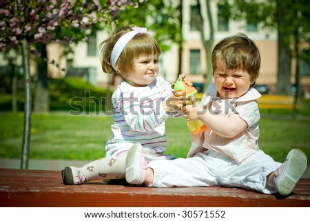two girls shared a bottle of juice - stock photo