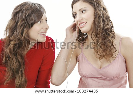 Two girls sharing earphones and listening to music. - stock photo