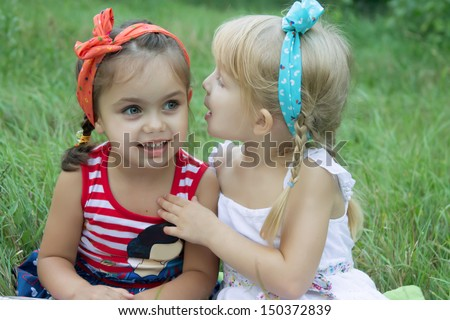 Two girls sharing secrets among grass - stock photo