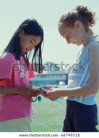 Two girls sharing toy - stock photo