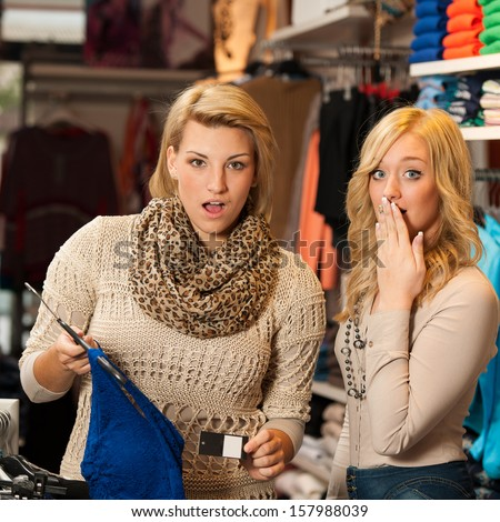 Two girls shocked by a price of clothes in a shop - women shopping - stock photo