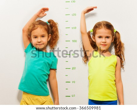 Two girls show height on wall scale at home - stock photo