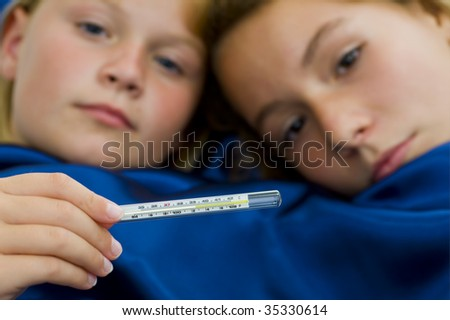 two girls sick in bed, having over 39?C /102?F fever. focus on thermometer with a shallow dept of field.