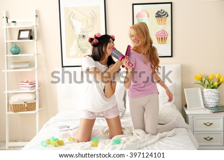 Two girls singing with combs on a bed in living room - stock photo
