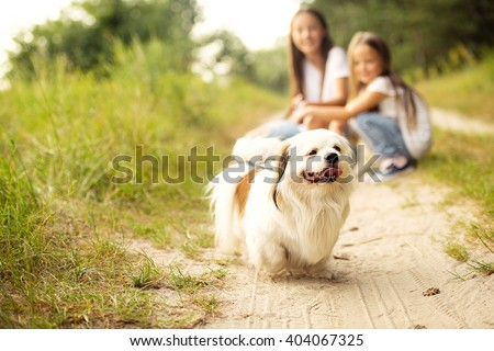 two girls sisters with their dog are walking outside - stock photo