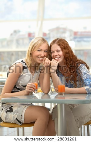 Two girls sit in cafe and smile, showing forward - stock photo