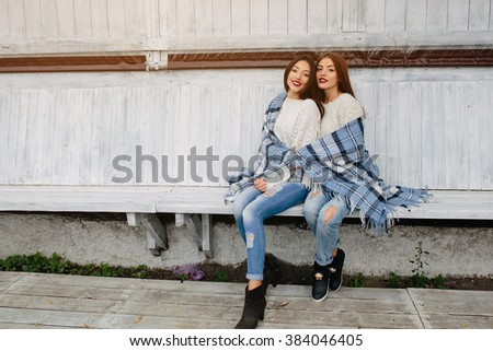 Two girls sit on a bench in the park and posing for the camera