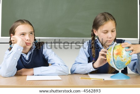 Two girls sitting at desk. On looking bored. Other is searching something on globe. Front view - stock photo