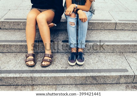 Two girls sitting in the city, one of them wear denim broken jeans and the other shorts. Only legs showing - stock photo