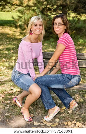 two girls sitting on a bench - stock photo