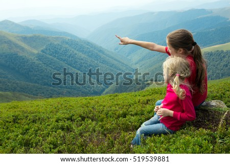 two girls sitting on a grass and  looking at the mountains