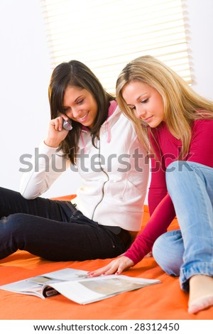 Two girls sitting on bed and browsing magazine. One of them talking by cellphone. - stock photo