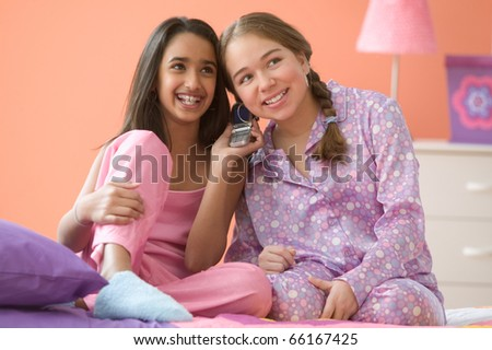 Two girls sitting on bed talking on cell phone - stock photo