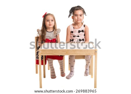 Two girls sitting on chairs at table and make wry mouths together isolated on white background - stock photo
