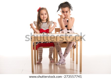 Two girls sitting on chairs at table and one of girls give thumb up and the other give thumb down - stock photo