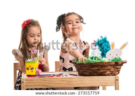 Two girls sitting on chairs at table and painting Easter eggs - stock photo