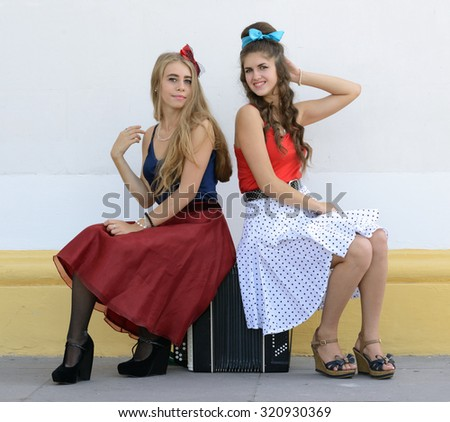 two girls sitting on old accordion - stock photo
