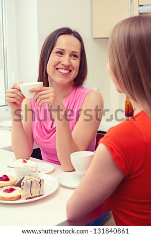 two girls sitting on the kitchen and talking - stock photo