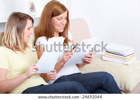 Two girls sitting on the sofa with paper notes and learning; one has got a brace