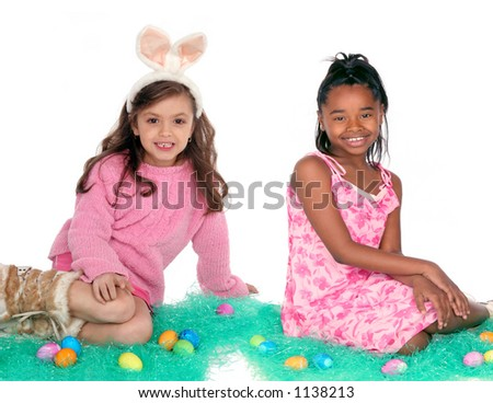 Two girls sitting with Easter eggs on green holiday grass - stock photo
