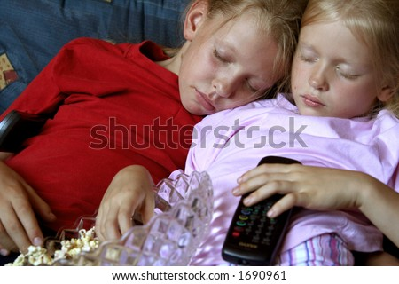 Two girls sleeping in front of TV set - stock photo