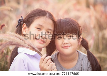 Two girls smiled brightly in the meadow , Asian Girl , Thailand.