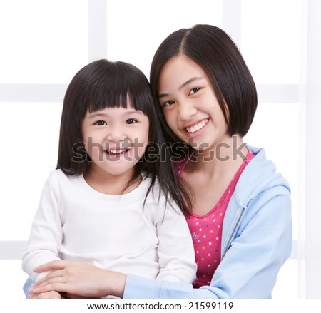 two girls smiling while looking to camera