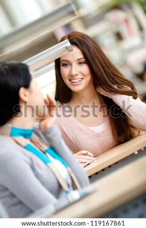 Two girls speak sitting at the desk at the library. Contact concept - stock photo