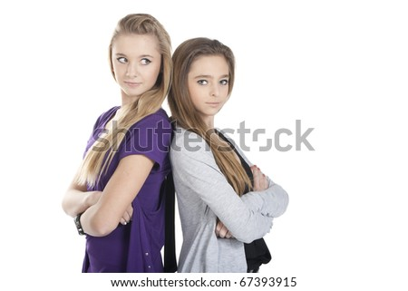 Two girls standing back to back not speaking to each other - stock photo