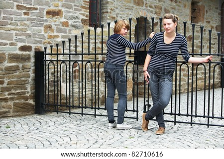 Two girls standing in front of closed gate - stock photo
