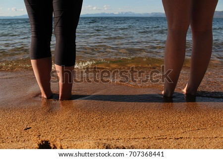 Two girls standing on the shore of an alpine lake with their feet buried in the sand.