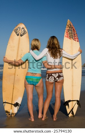 Two girls standing with surfboards at dawn looking out to the ocean - stock photo