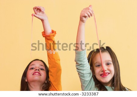 Two girls stretching a chewing gum from they're mouth - stock photo