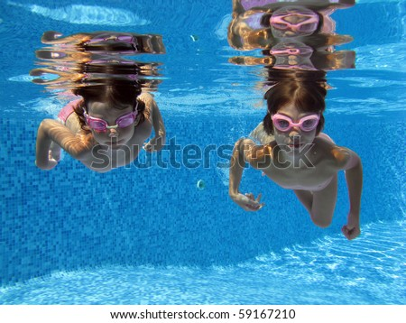 Two girls swimming underwater in the pool - stock photo