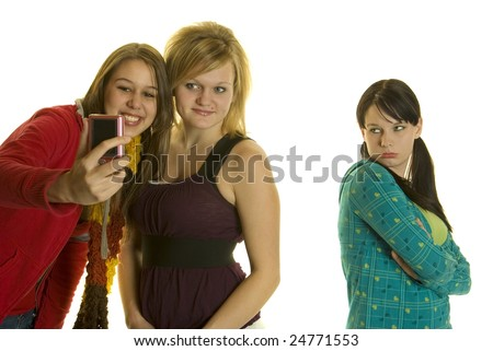 two girls take photo  or video with cell phone camera third girl left out - stock photo