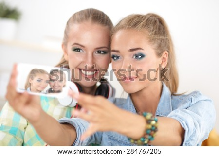 Two girls taking pictures on the phone