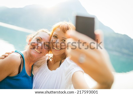Two girls taking self photograph - stock photo