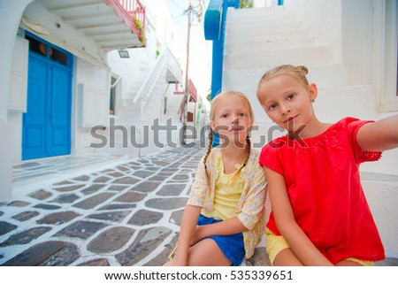 Two girls taking selfie photo outdoors in greek village on narrow street