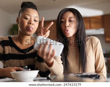 two girls taking selfies with silly faces on smartphone - stock photo