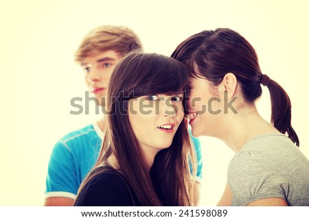 Two girls talking gossip about boy - stock photo