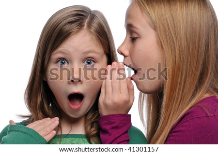 Two girls telling a secret and expressing surprise isolated on white - stock photo