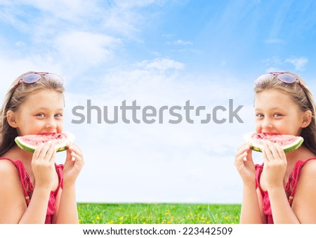 two girls twins eating watermelon on blue sky background - stock photo