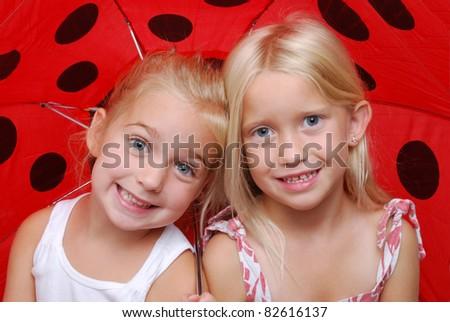 two girls under a umbrella - stock photo