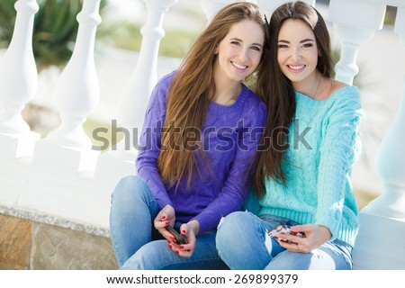 Two girls using smartphones outdoor. Two funny women friends laughing and sharing social media videos in a smart phone outdoors.  - stock photo