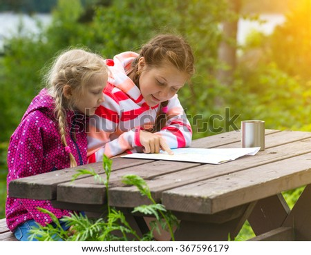 two girls view the map of sitting over wooden table, Norway - stock photo