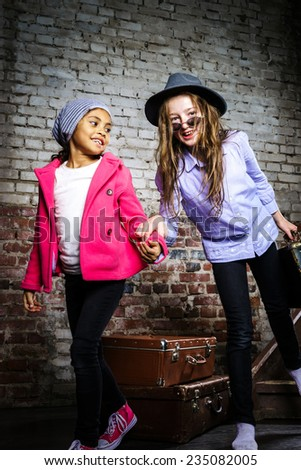 Two girls waiting for the train with vintage suitcases - stock photo