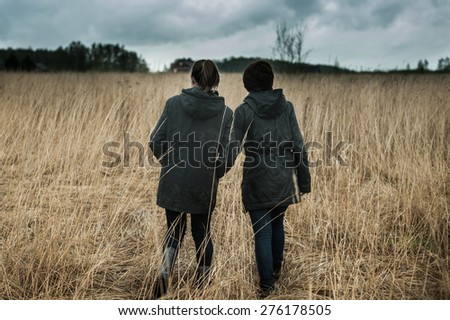 Two girls walking across the field in a thunderstorm - stock photo