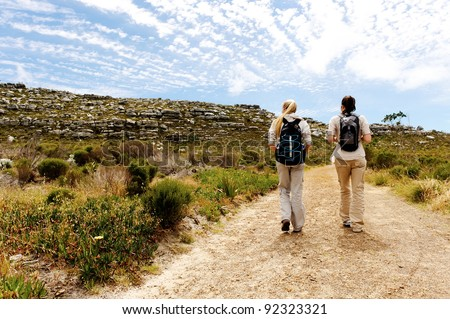 two girls walking outdoors and having fun exploring the wilderness - stock photo
