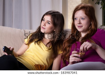 Two girls watching movie and eating snacks - stock photo