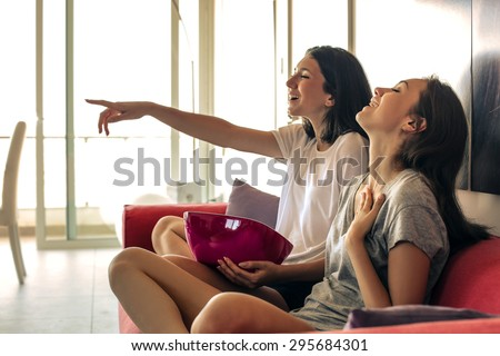 Two girls watching tv together - stock photo